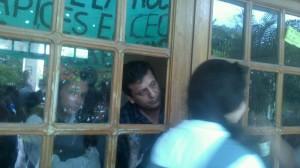 Hombre de civil, desconocido por alumnos, custodiando el colegio.